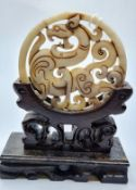 "A Chinese carved white (""Hotan"") jade disc (amulet?) with mythical beasts on a custom made wooden"
