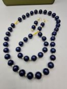 A lapis lazuli and South China Sea pearls necklace, bracelet and earrings set in a presentation box.