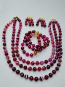 A three row striped red agate necklace, bracelet and earrings set in presentation boxes. Necklace