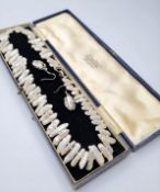 An unusual pearl necklace and assorted earrings in original presentation box. Pearls on a