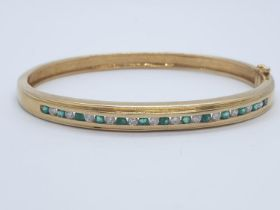 18CT Y/G DIAMOND & EMERALD BANGLE CHANNEL SET, WEIGHT 20G WITH 0.25CT DIAMONDS & 0.60CT EMERALD