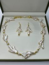 A very unusual Keshi pearls necklace and earrings set in the shape of bird?s feet. In a presentation