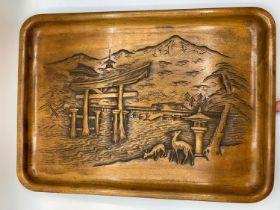 A wooden tray with relief carving of Itsukushima Shinto Shrine in Japan. It depicts the Torii (