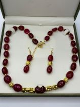 An impressive, large beaded, ruby and gold filled necklace and earrings set in a presentation box.