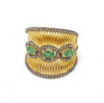 A gold and silver ring with 3 Colombian emeralds and over 150 diamonds (tested) on parallel,