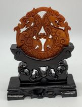 A Chinese, hand carved on both sides and pierced, orange hard stone amulet representing two
