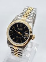 ROLEX Oyster Perpetual Datejust ladies watch with black face and two tone steel strap, 22mm case