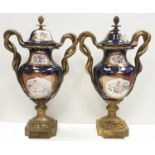Pair of Grecian style Urns with serpent handles and recoco trim. Very nice condition. Would