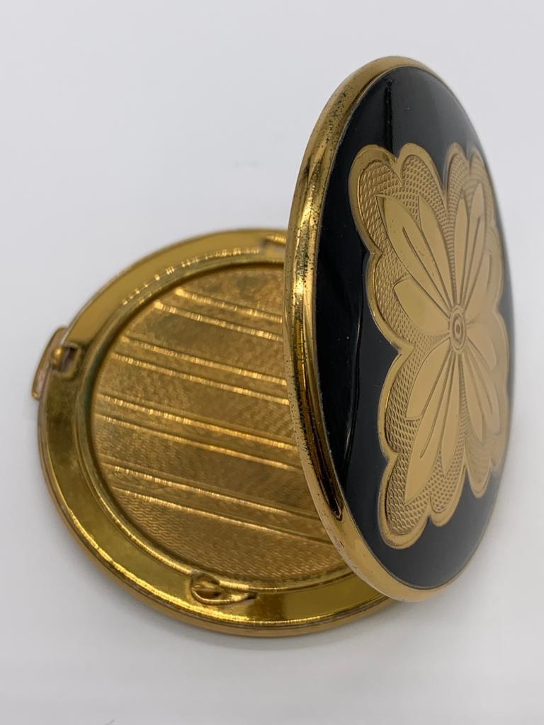 Vintage 1950/60's compact by Melissa. Black enamel lid with gold feature engine turned base.