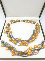 A very unusual necklace and bracelet set with large yellow-orange pearls. In a presentation box.