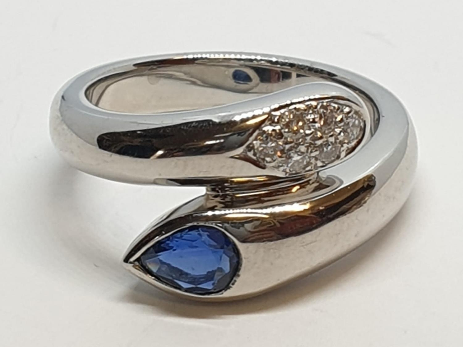 Platinum cross over ring with 0.60ct Thai sapphire and 0.30ct encrusted diamonds, weight 13.7g and