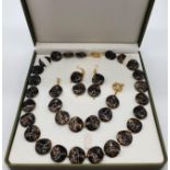 A 60?s black and gold coloured necklace, bracelet and earrings set in a presentation box. Necklace