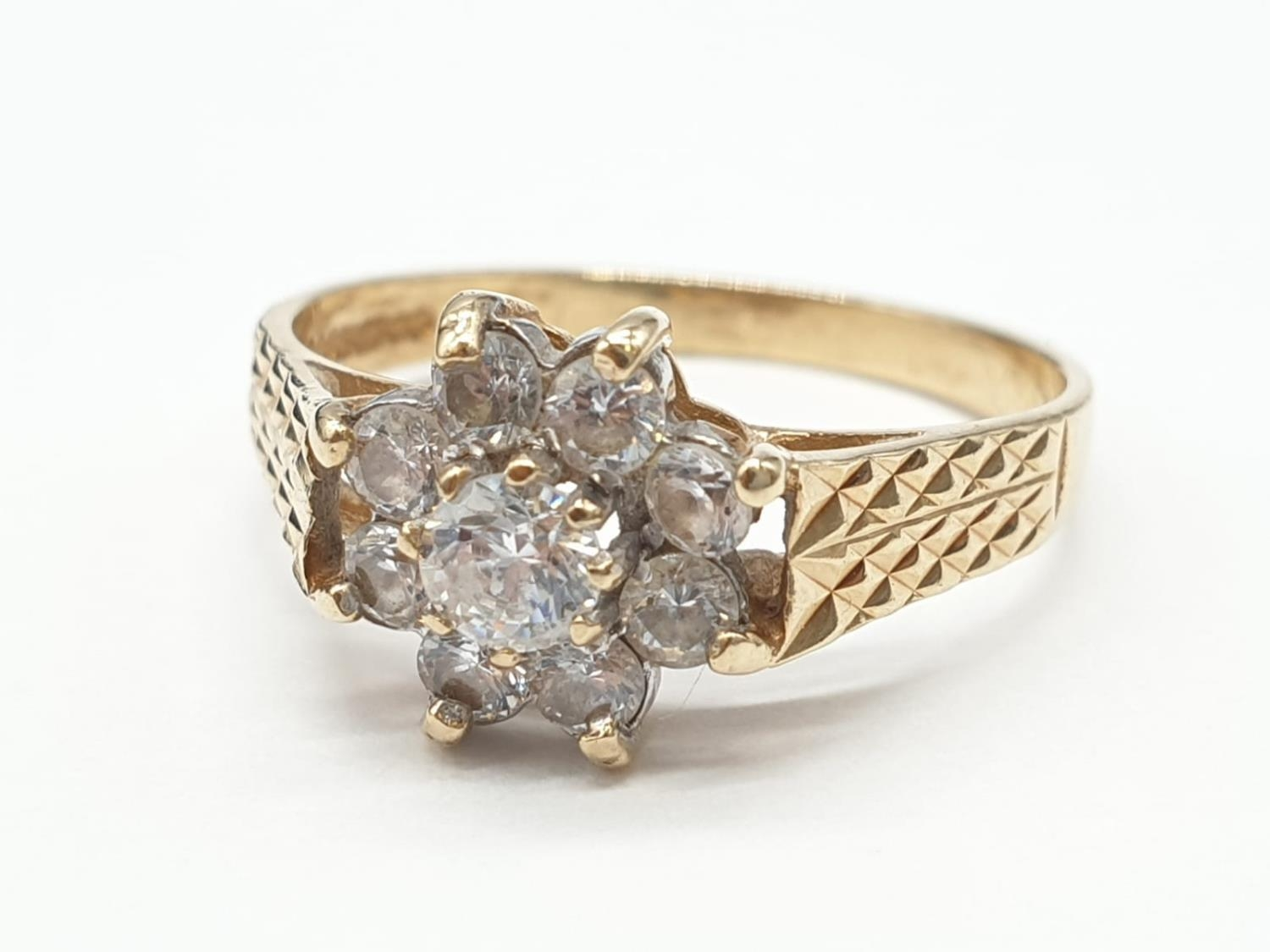9ct Gold ring having cubic zirconia cluster to top in claw mounts and chased design work to