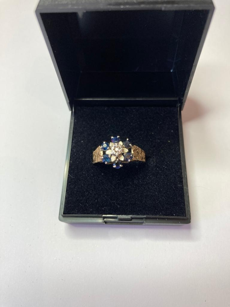 9ct Gold and Sapphire ring having six sapphires in a flower setting with illusion set diamond to