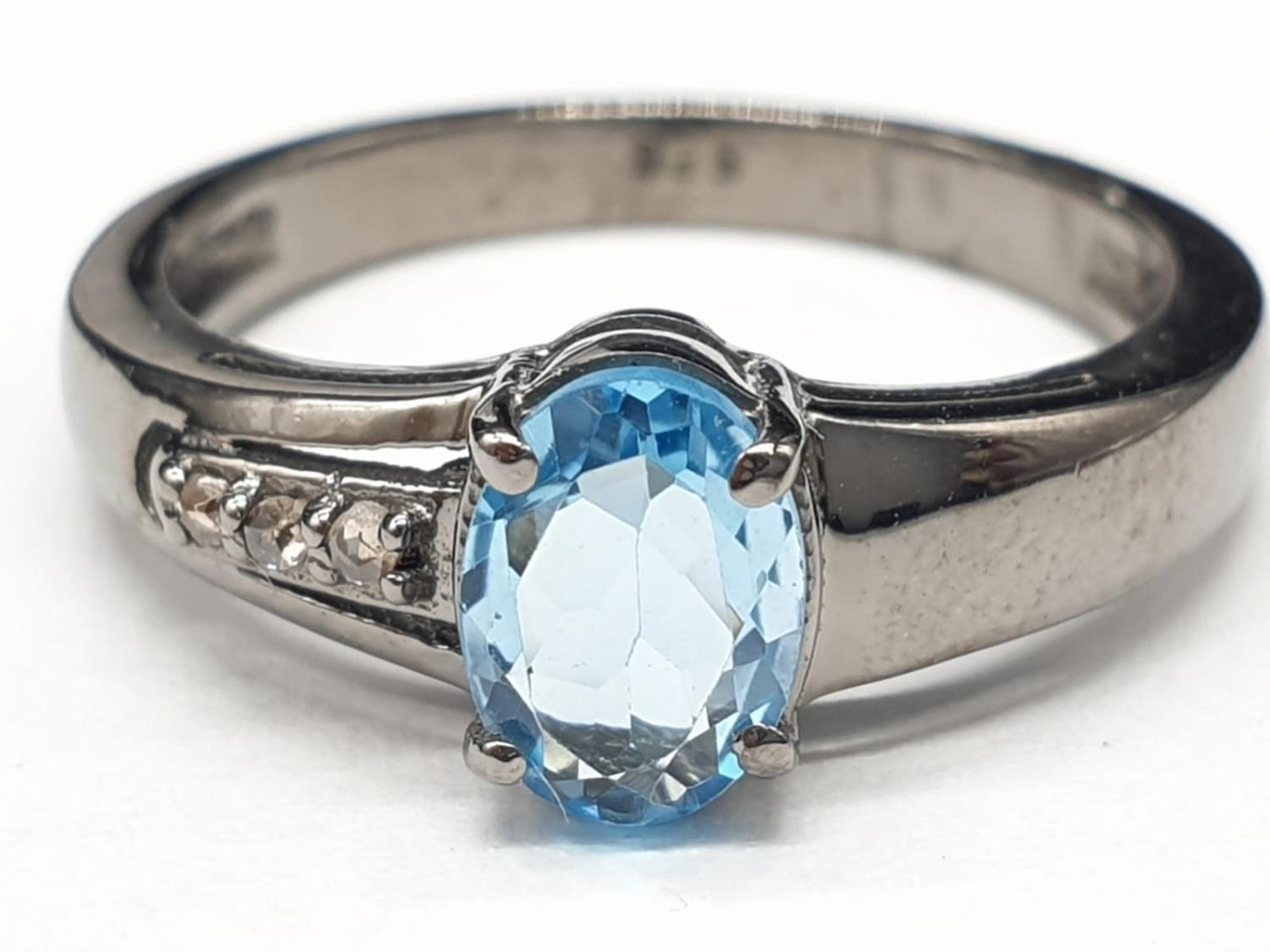 0.86 Ct Blue topaz stone inset a blackened silver ring. With 0.05 Ct rose cut diamonds, weight 2.35g