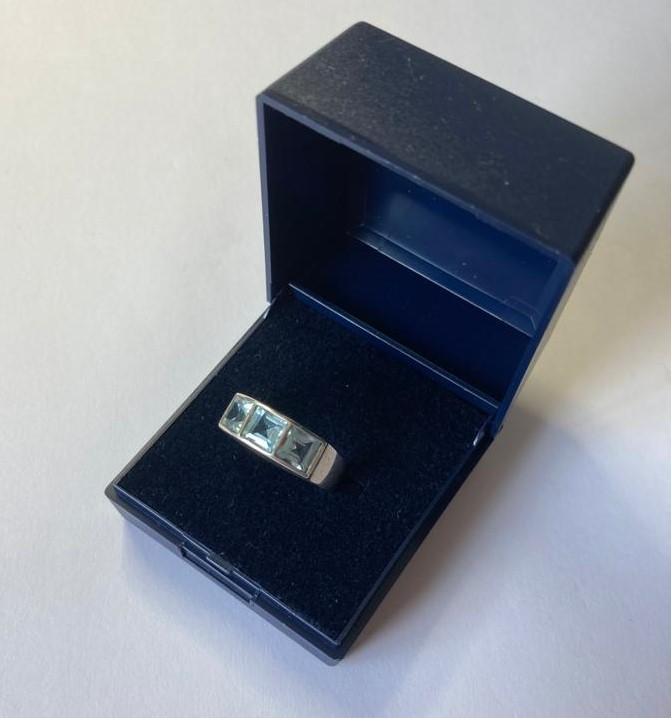 Silver ring having 3 channel set blue topaz stones. Size N.