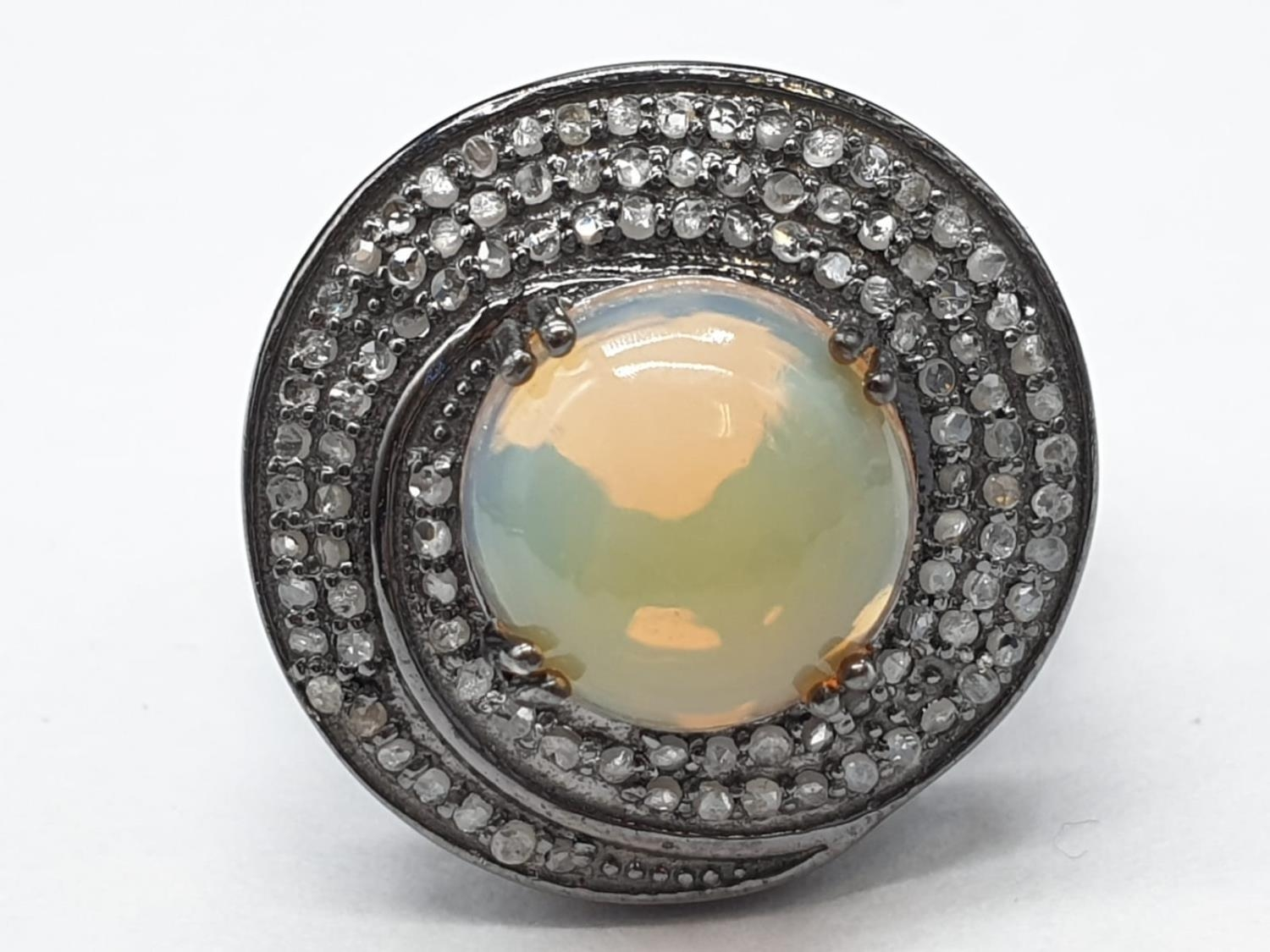 3.50Ct Fire Opal set within a blackened silver ring, with 0.55Ct rose cut diamonds, WEIGHT 6.92G and