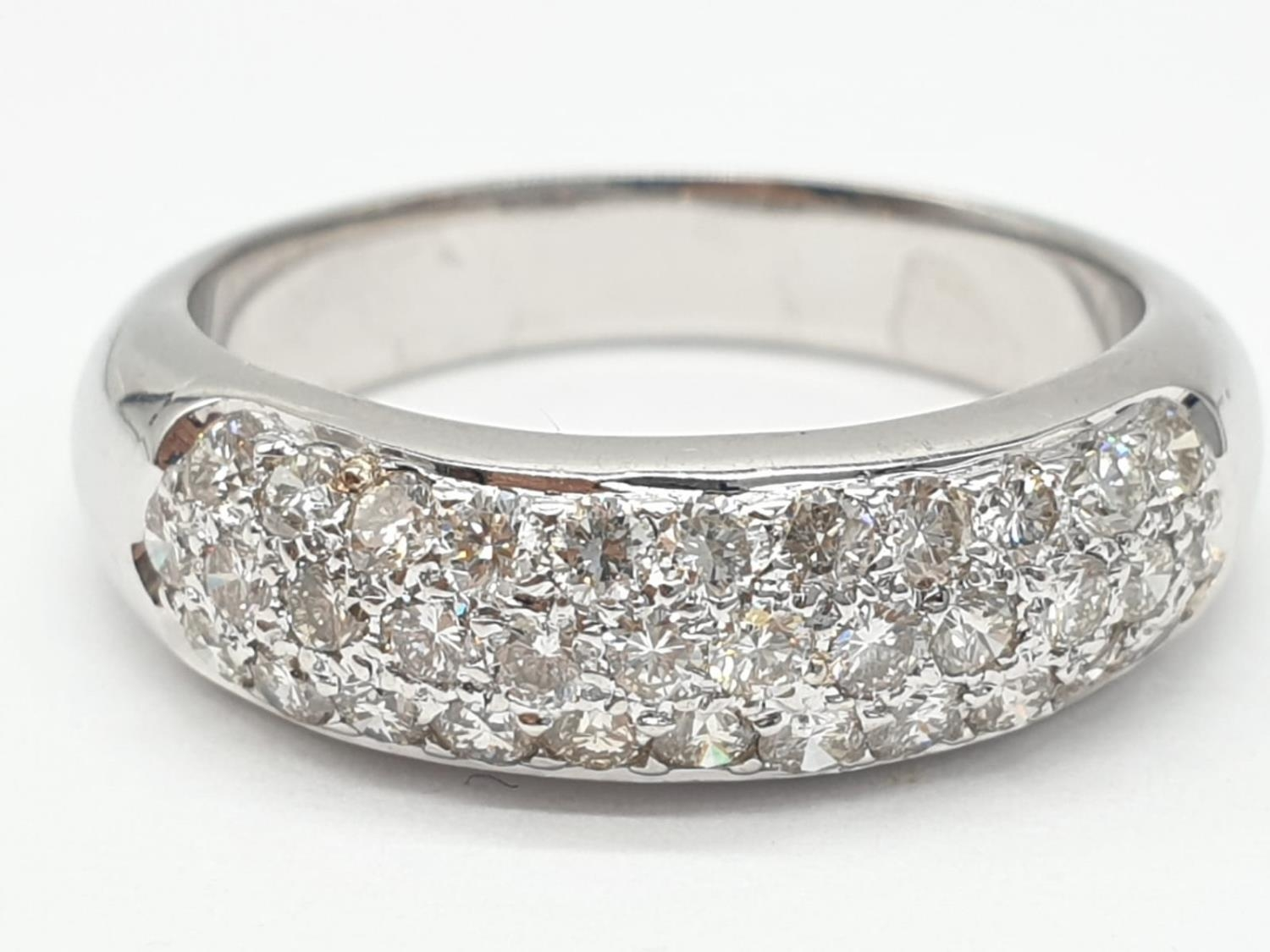 A diamond encrusted 18ct white gold ring. 6.4g and size N.