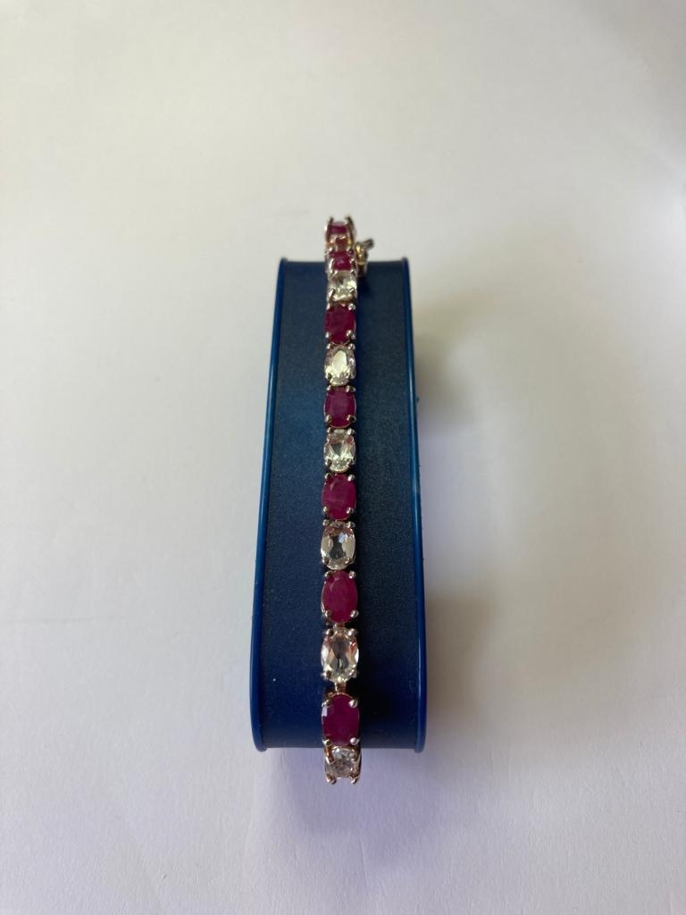 Silver tennis bracelet with pale aqua and pink spinel stones set in four claw mounts. 925 silver.