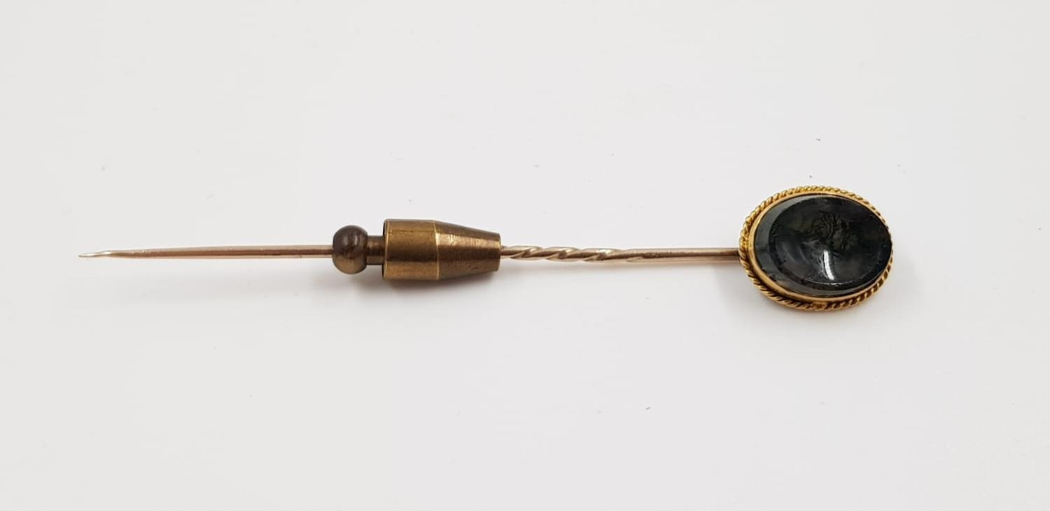 A yellow metal stick pin with agate head. Weighs 3.4g and is 7cm.