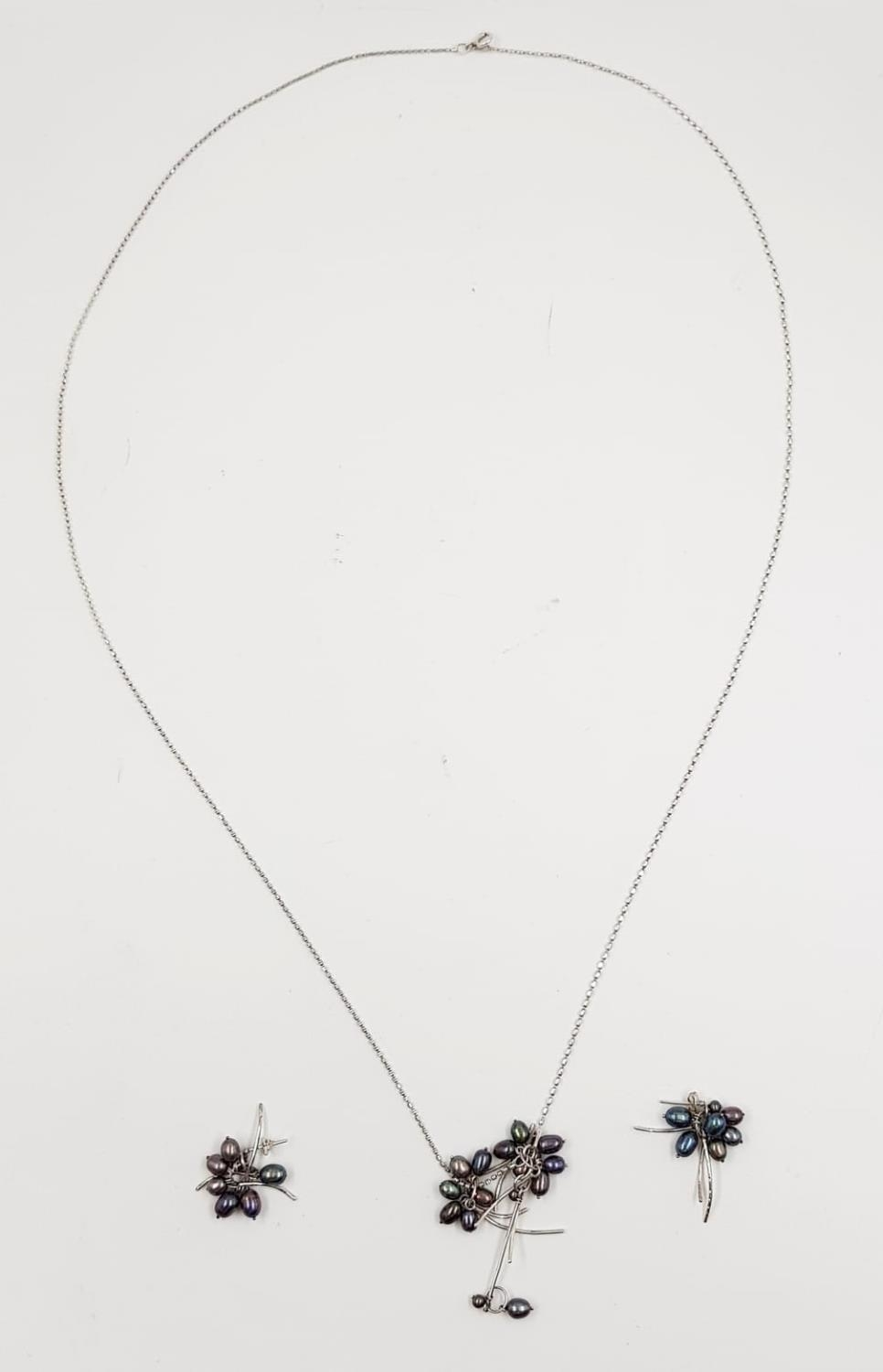 A black pearl and silver necklace with earring set. Weighs 15.4g and length is 84cm.