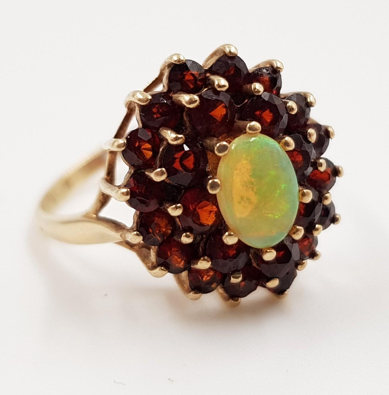A 9ct gold, fire opal and garnet stone cluster ladies ring. 3.4g total weight. Size P.