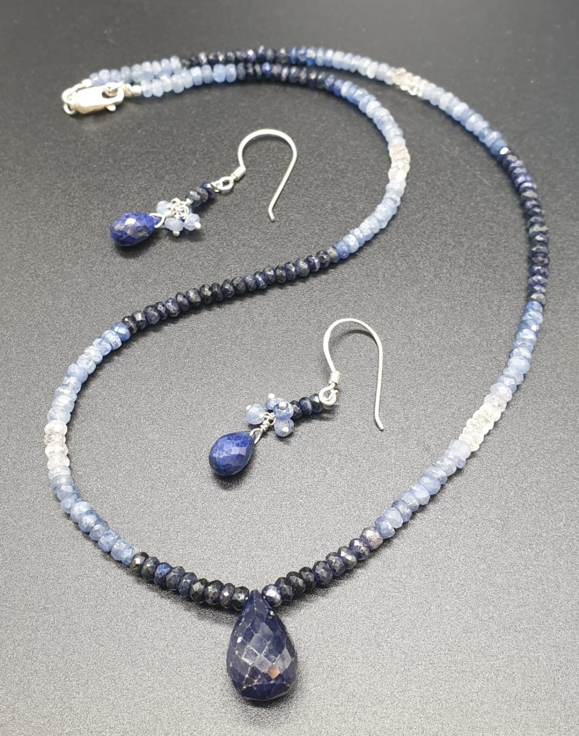 A shaded Blue sapphire Necklace with a sapphire drop and matching dangler earrings. Necklace