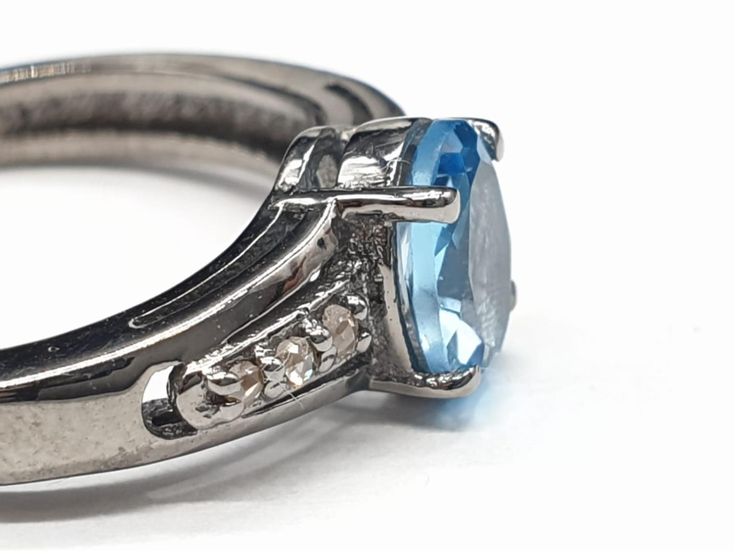 0.86 Ct Blue topaz stone inset a blackened silver ring. With 0.05 Ct rose cut diamonds, weight 2.35g - Image 2 of 7