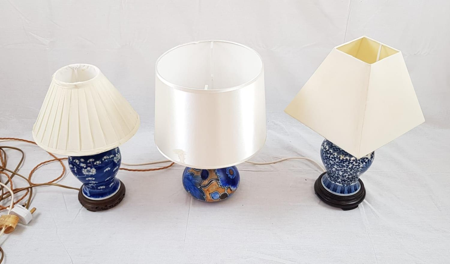 3 Ceramic table lamps with shades. Two are Chinese with a blue decorative glaze. The third is a
