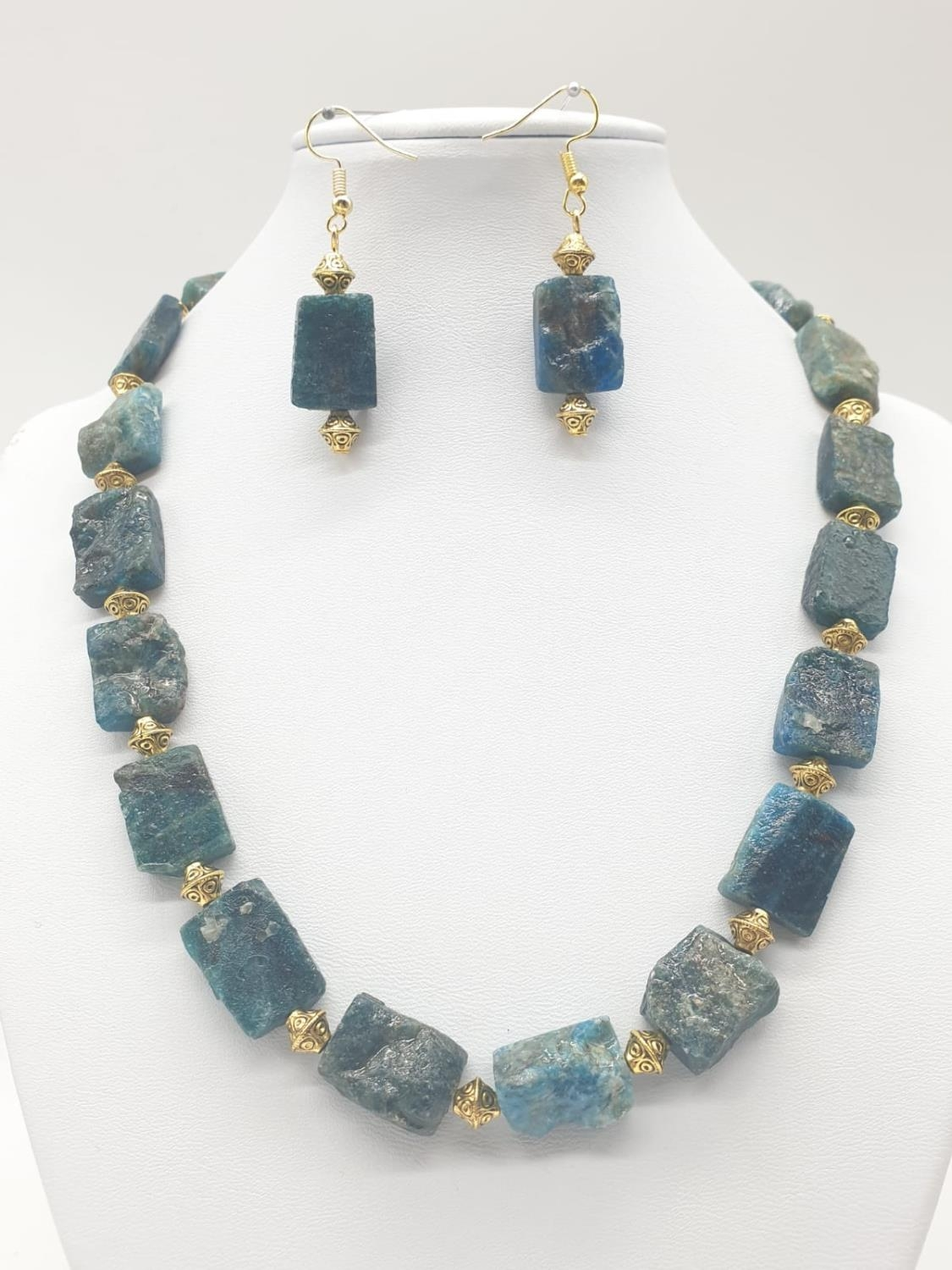 A necklace and earrings set made of Brazilian bluish apatite in its natural state. In a gift box,