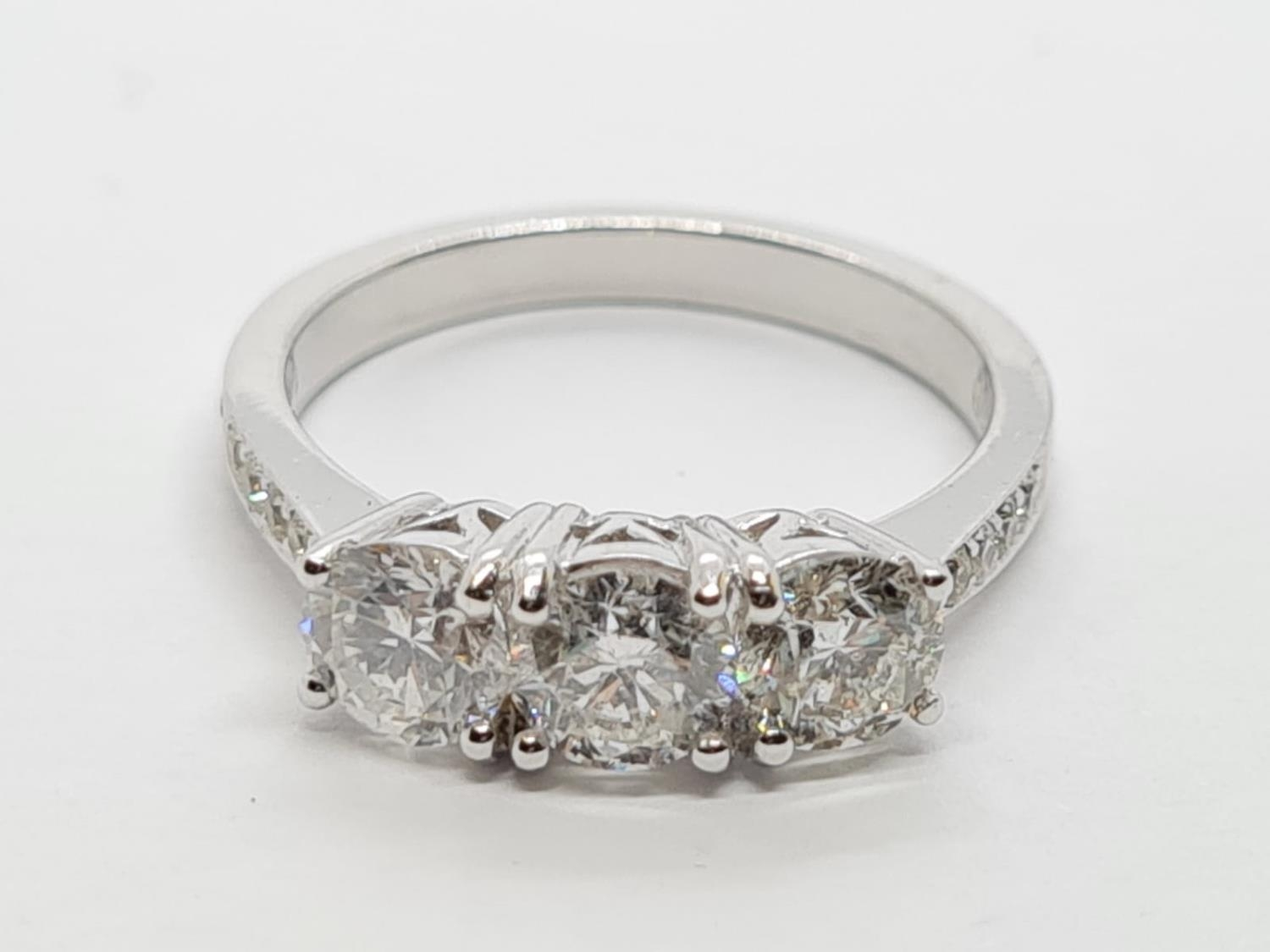 18ct White Gold with Trilogy set of 1.5ct Diamonds and further encrusted diamonds on the shoulder.