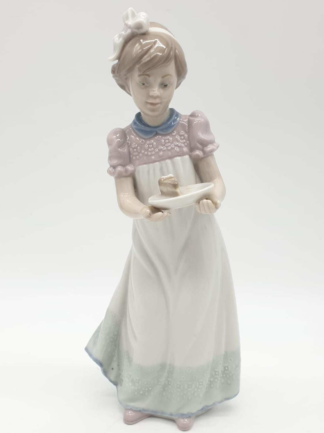 Lladro girl holding a cake on a plate. 20cm tall.