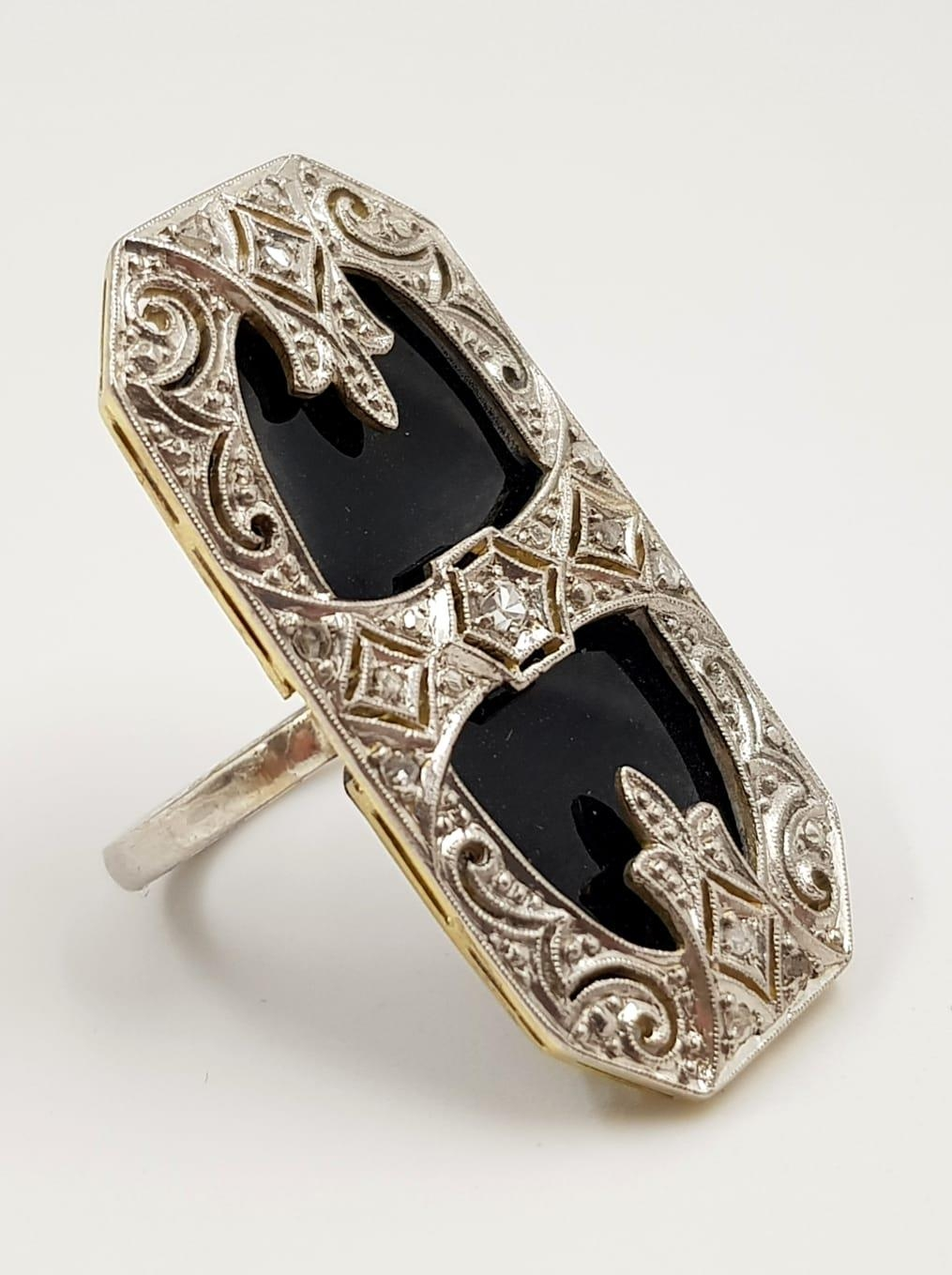 An art deco, platinum and black onyx ring. 6.6g total weight and size J.