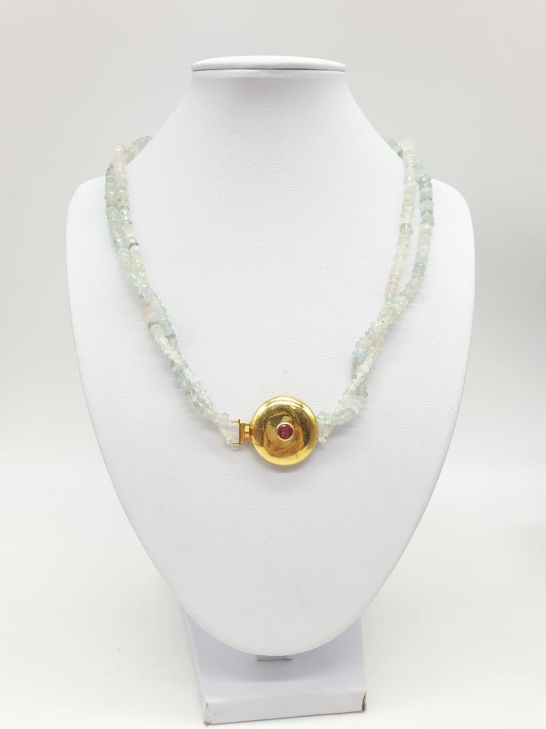 An aquamarine necklace with a gold plated silver clasp, tourmaline stone at the centre of clasp.
