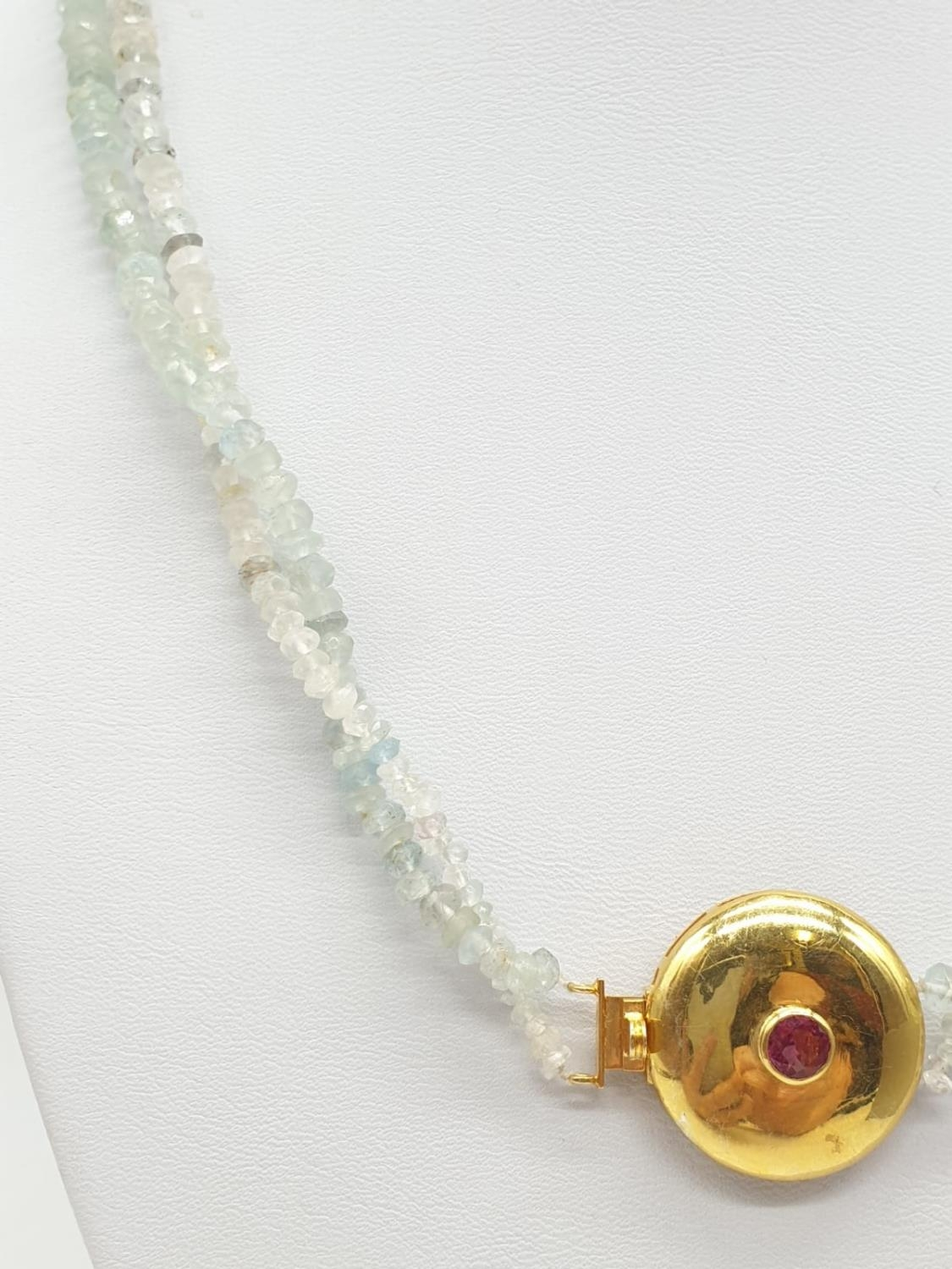 An aquamarine necklace with a gold plated silver clasp, tourmaline stone at the centre of clasp. - Image 4 of 5