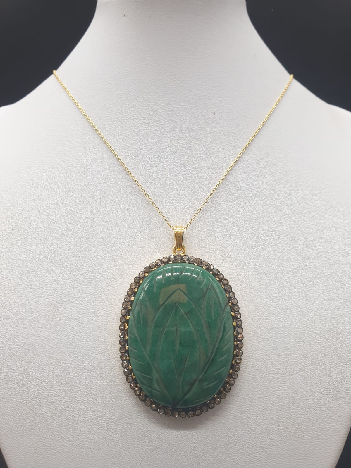 A carved emerald Pendant with a halo of rose cut diamonds in pave setting in sterling silver with