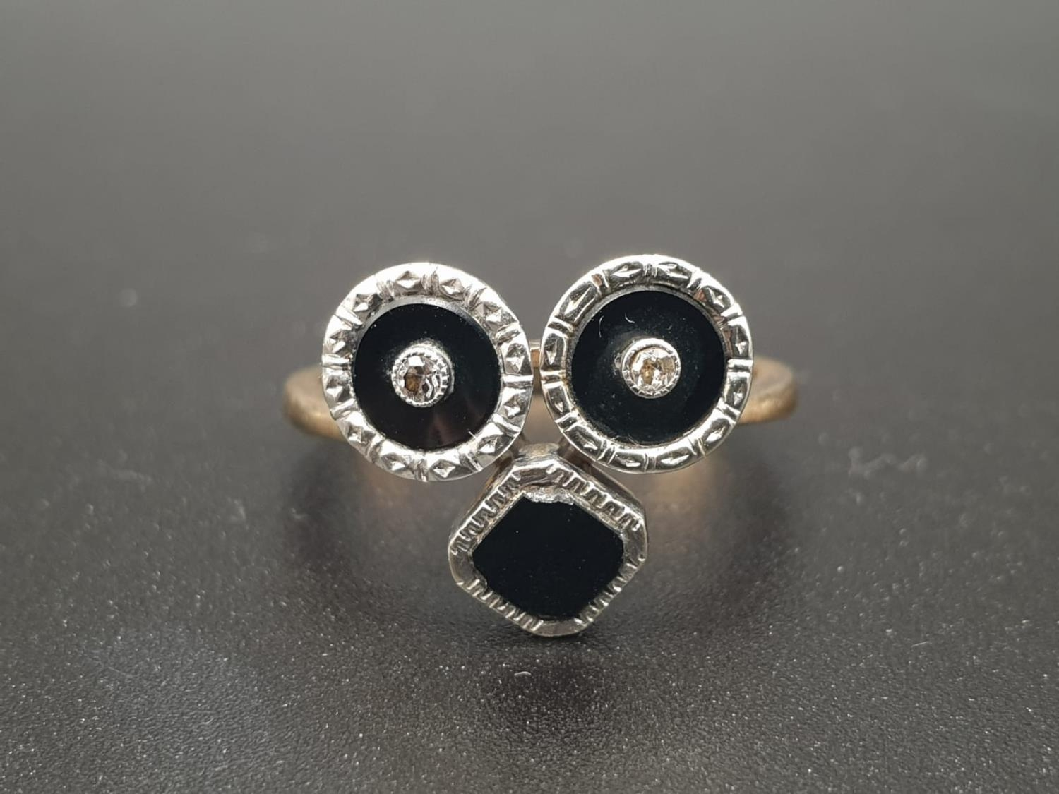 A 9K GOLD RING WITH BLACK ENAMEL AND DIAMONDS USED TO FORM THE SHAPE OF A FACE. 3.3gms size O