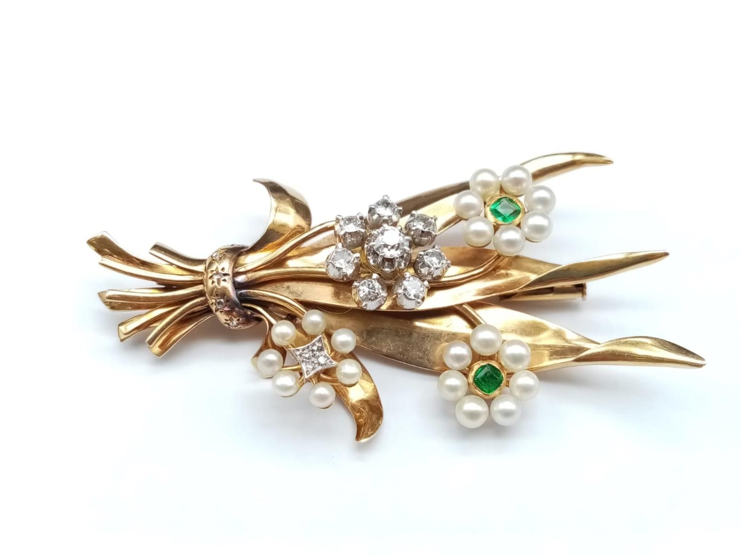 AN INTERESTING 18K GOLD BROOCH FASHIONED IN A FLEUR DE LYS STYLE WITH DIAMONDS, EMERALDS AND SEED