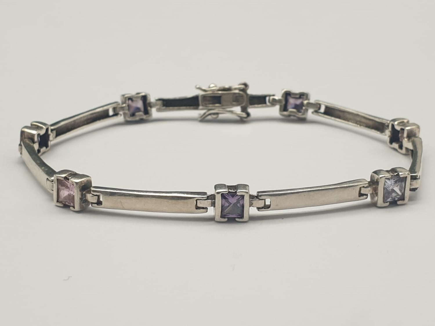 A SILVER ARTICULATED BRACELET WITH PINK, WHITE AND PURPLE STONES. 9.4gms 18cms