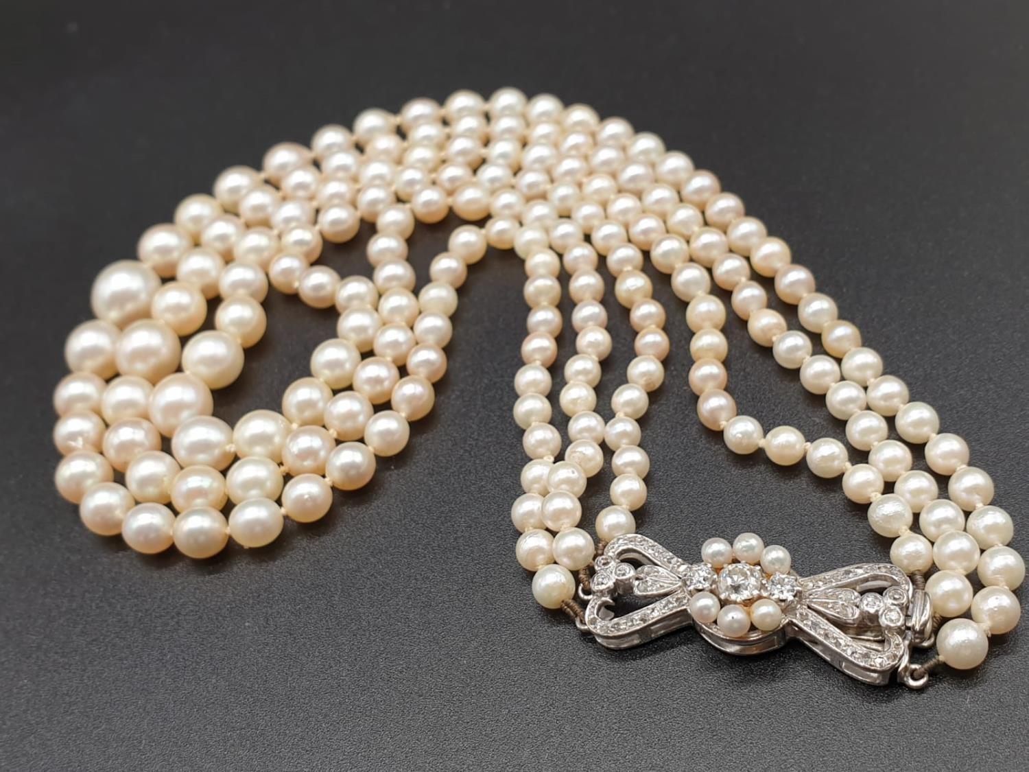 A 3 ROW GRADUATED PEARL NECKLACE WITH PLATINUM AND DIAMOND CLASP 48gms and 18cms in length