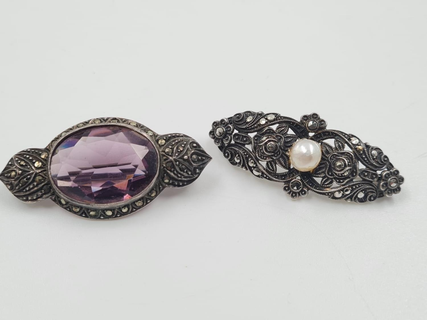 2 Silver Marcasite Brooches. One with a large Hamethyst the other a Pearl. 4cm. 18g total weight.