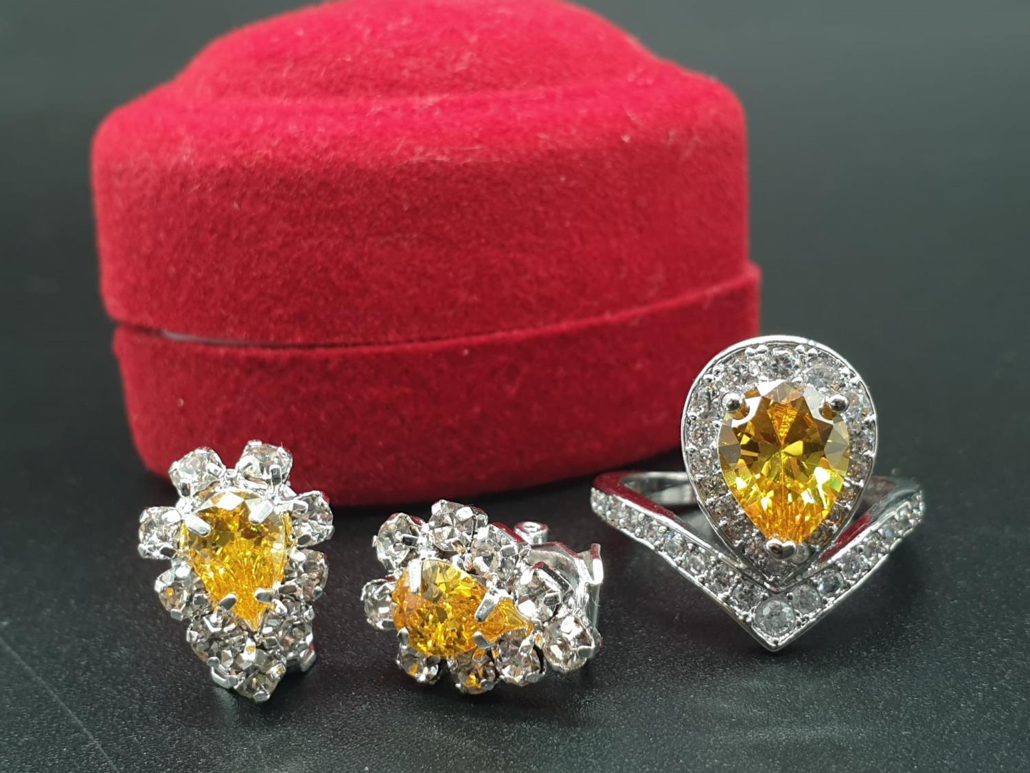 A white metal ring and earrings set with yellow topaz and clear sapphires. Ring size: N. Presented