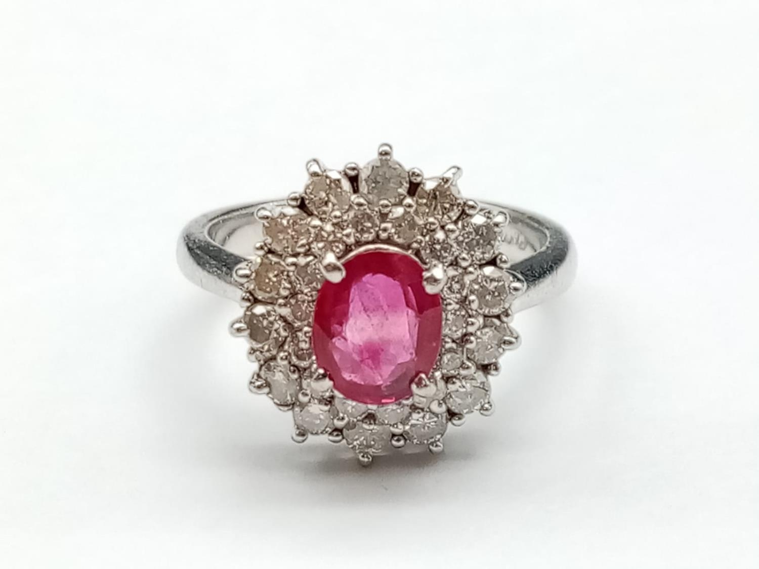A PLATINUM RING WITH PINK RUBY CENTRE STONE WITH DIAMOND SURROUND. 6.5gms size K/L