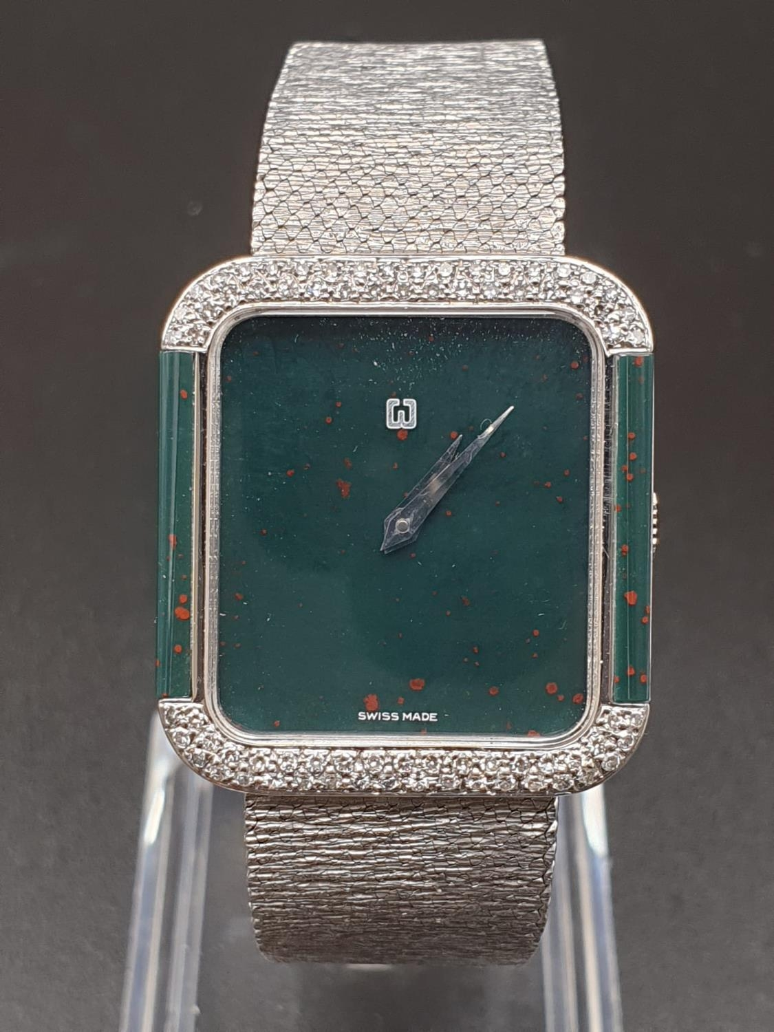 AN 18K WHITE GOLD DRESS WATCH WITH HALF DIAMOND BEZEL AND SOLID GOLD STRAP. 26MM