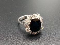 AN 18K WHITE GOLD RING WITH LARGE 2.85ct SAPPHIRE CENTRE STONE SURROUNDED BY BRILLIANT DIAMONDS.