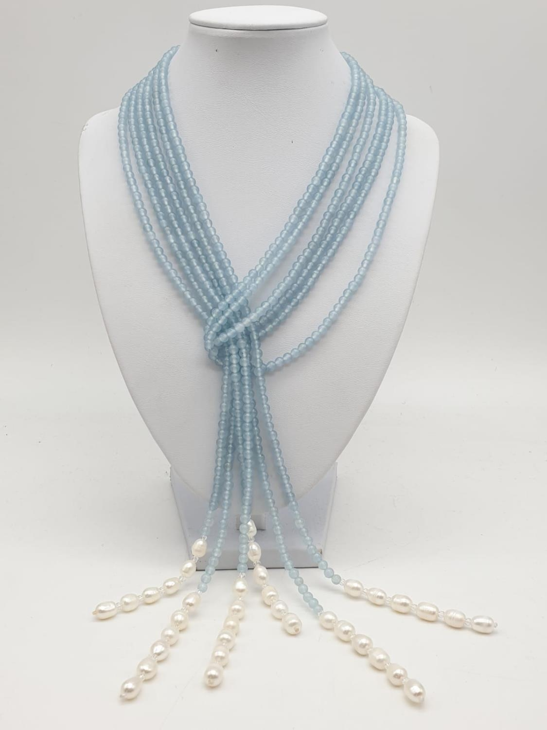 Three very long rows (128cm!) of aquamarine (colour enhanced) and natural pearls that can form a