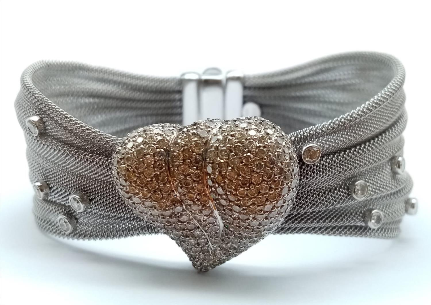 an 18k white gold bracelet with 10 diamonds and a diamond encrusted heart. 53.4gms 19cms