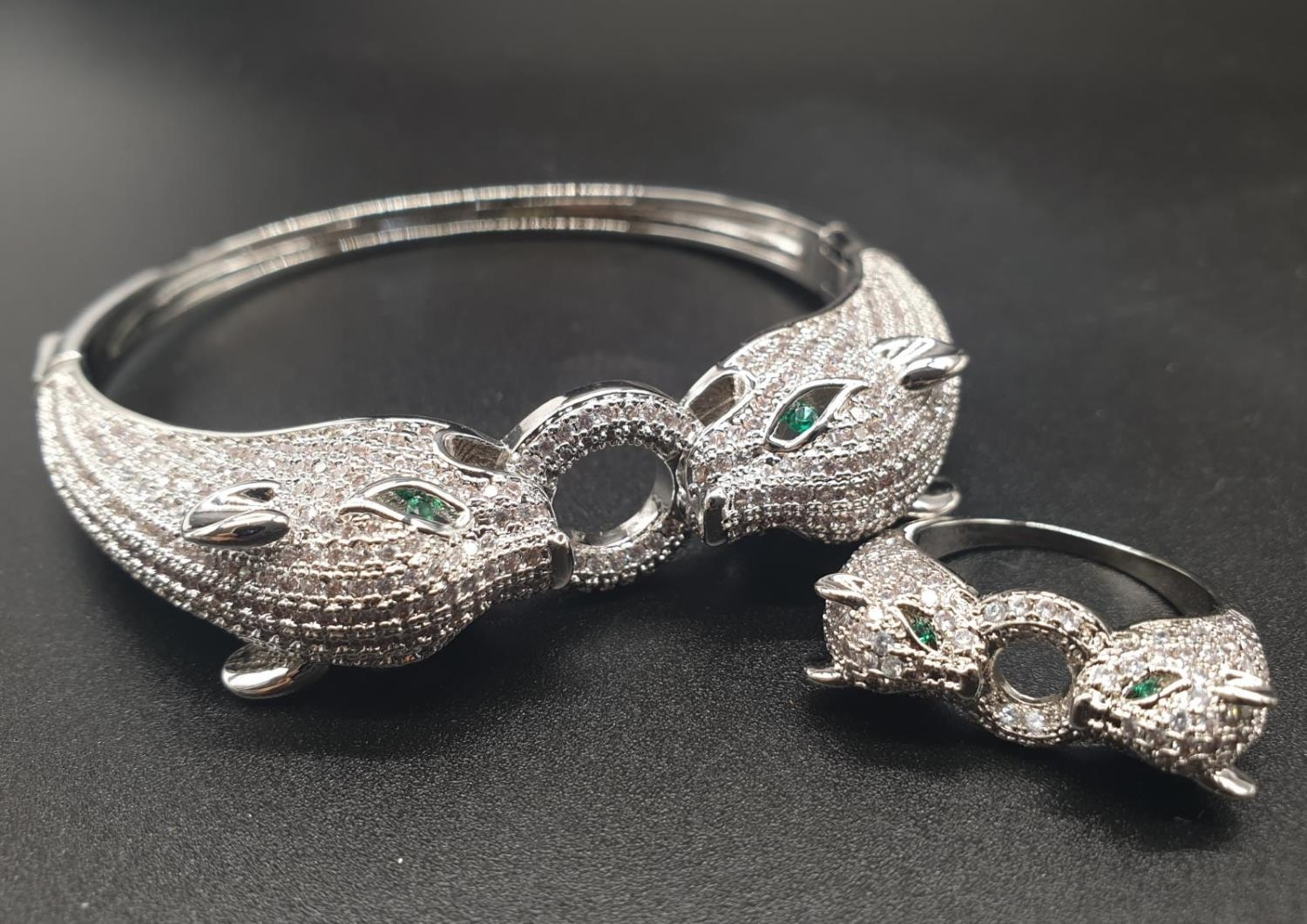 A white metal (untested) Cartier Panther style bracelet and earrings set In a presentation box. Ring
