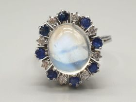 18k white gold ring set with a large moonstone/sapphire centre and surrounded by diamonds and