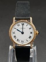 18k gold Cartier ladies wristwatch with white round face and diamond bezel, black leather strap.